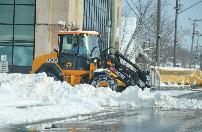 A loader clears snow from the corner of Duke and Henderson streets in downtown Chatham Feb. 23 following a storm. Miramichi city council has extended the snow removal contracts for five neighbourhoods for another year.