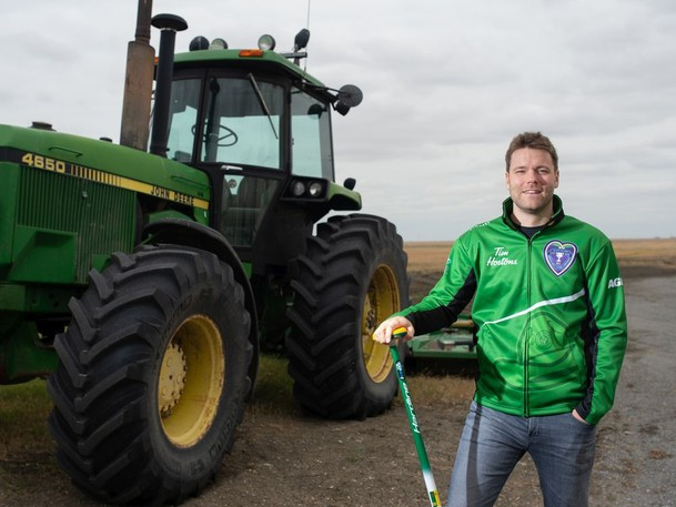 Kirk Muyres, a provincial curling champion, stands in a farm yard south of Regina, Saskatchewan on August 18, 2021. Muyres is also involved in an initiative that supports mental health in agriculture.