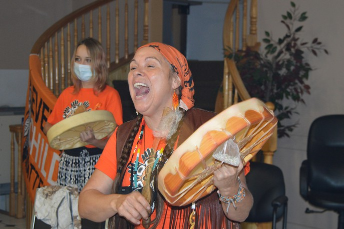 Pabineau First Nation recognized the first National Day for Truth and Reconciliation with a ceremony at the community band hall Thursday. Pictured Traditional Knowledge Keeper Marie Kryszko drumming Yo Way Hi Ya, a friendship song. Her granddaughter Maria Aubie is pictured in the background.