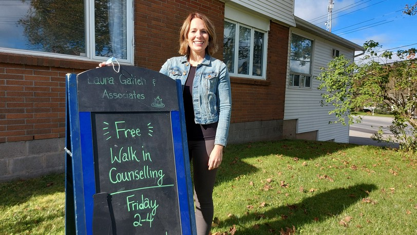 Laura Gatien stands with the sign that started it all two years ago. Since September 2019, Gatien's clinic has been able to offer free counselling to anyone that needs it every Friday from 2-4 p.m.