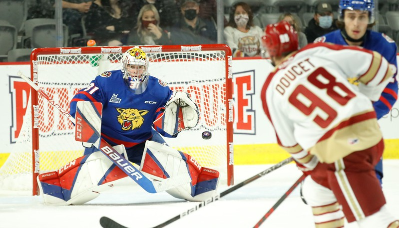 Moncton Wildcats goaltender Vincent Filion and defenceman Ethan Dollemont watch Acadie-Bathurst Titan forward David Doucet shoot the puck during QMJHL play on Saturday at the Avenir Centre.