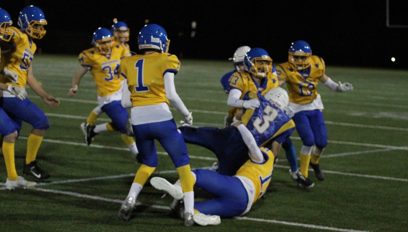 Oromocto High Blues' Kalob McLaughlin (No. 3) is stopped by Mathieu-Martin Matadors players Gabriel Levesque, bottom, during a New Brunswick High School Football League game on Friday at Rocky Stone Memorial Field.