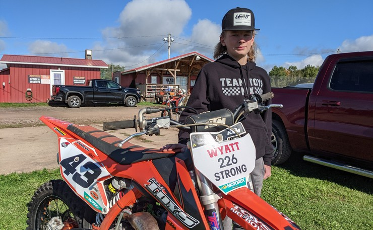 Marcus Dureen stands next to his K2m motorcycle at the Riverglade Motocross near Salisbury Sunday morning. Dureen was there to support his friend Wyatt McQuinn who was badly injured on the track two weeks ago.