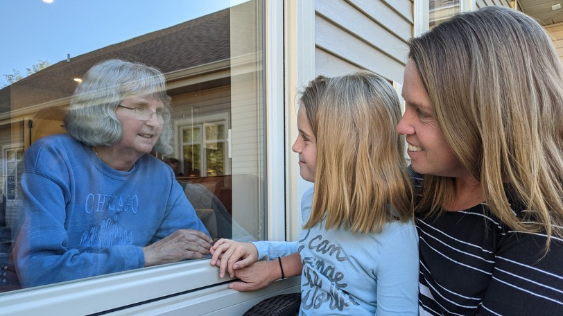 Tracy Dunn and her daughter Molly Morash smile through a window at her mother Della Dunn, who is a resident of the Grass Home on Coverdale Road in Riverview. Visitor restrictions mean they can see each other through a window, or sit in the yard wearing masks and distancing without physical contact.