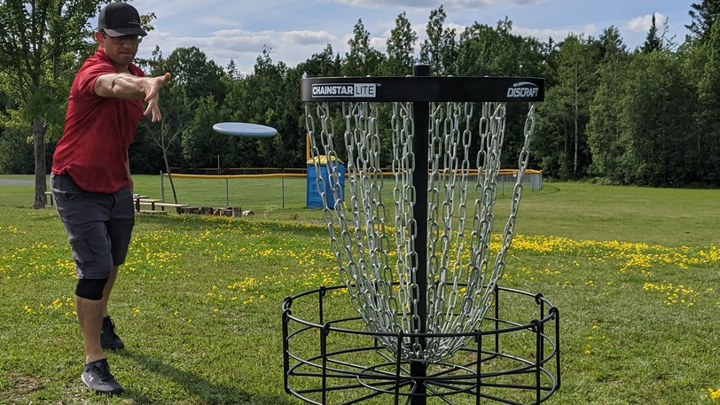 Photo from July 2021 shows Blake Reynolds, a disc golf enthusiast from Riverview, throws a disc at a basket in the playground of Claude D. Taylor School. The chains stop the disc and it falls into the cage below, creating a rattling sound.