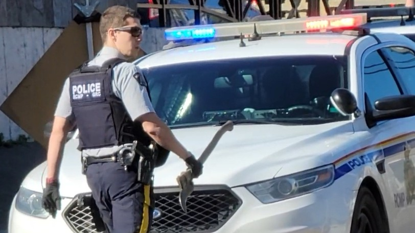 An RCMP officer carries an axe that was taken from a car that was reported stolen Tuesday morning. The car was recovered on Wesley Street Tuesday afternoon and two people face charges of possession of stolen property.