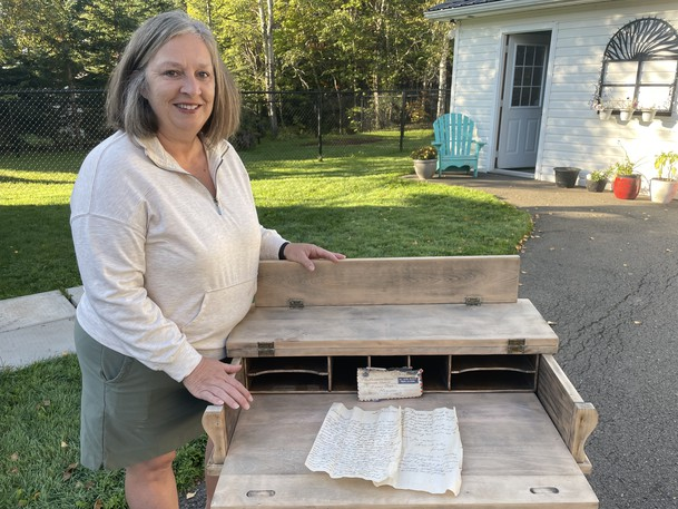 Gail Duffy stands next to the desk she bought off Facebook Marketplace this summer. On the desk is a letter she found stuck in the back of the desk dated January, 1951.