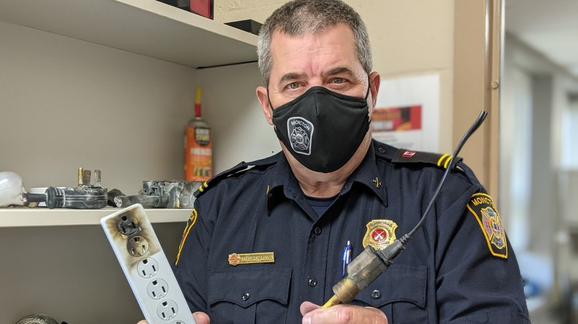 Steve Richardson, fire prevention officer with the Moncton Fire Department, shows a charred power bar and extension cords from the wall of fame at the St. George Boulevard fire station.