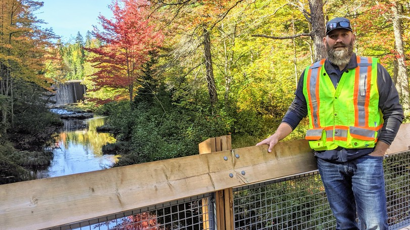 Eric Hopper, manager of recreational facilities and assets for the Town of Riverview, stands on a bridge in the Mill Creek Nature Park Wednesday. The waterfall of the dam can be seen in the background.