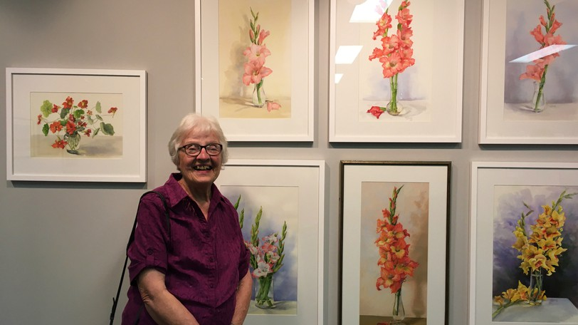 Mount Pleasant artist Irene Tompkins with a selection of her paintings of flowers at the Andrew and Laura McCain Art Gallery.