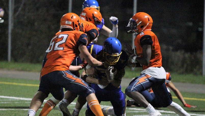 Mathieu-Martin Matadors' Samuel Parent, middle, is blocked close to the goal line by L'Odyssée Olympiens defenders Cédric Manuel (No. 52), Jacob Taylor and Régis Mbifo (4) during the New Brunswick High School Football League's Acadie Bowl on Thursday at Rocky Stone Memorial Field.