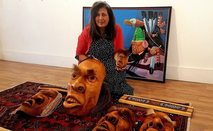 Nadia Khoury, owner of Gallery on Queen, holds some of the more than 100 pieces of art from Indigenous artists throughout Atlantic Canada bound for a major show in Toronto. The masks are creations of the late Ned Bear, while the belts are from artist Chantal Polchies. In the background is a painting from the collection of the late Roger Simon.
