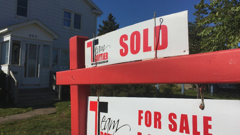 Unusually high activity in the local real estate market has caused property assessments to rise, prompting city officials to plan for a reduced tax rate. For sale and sold signs are shown outside a house in Sunny Brae on Saturday.