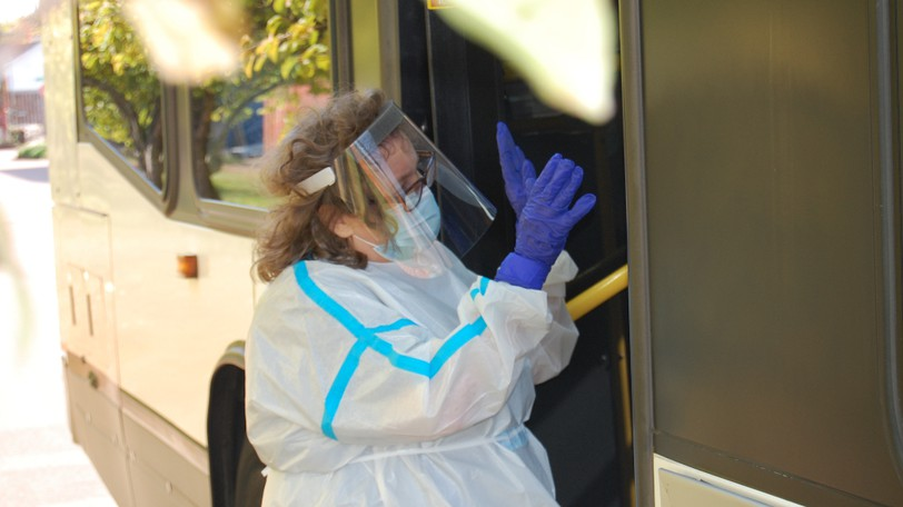 Sue MacDonnell, a case manager at Harvest House, waves to passengers on a shuttle on Oct. 10, 2021, moments before they departed from an alternate shelter at the Lions Club on Mark Avenue, established following an outbreak at Moncton's Harvest House.