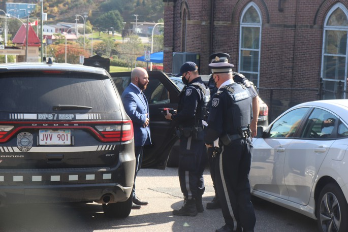 Sometime after 11 a.m., fivepeace officer vehicles arrived on the scene where they escorted a bald man with a beard, wearing a blue suit to oneof the vehicles where he was released several minutes later