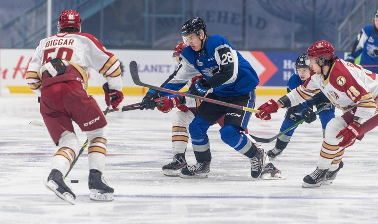 William Dufour of the Saint John Sea Dogs (28, blue) battles with Jaxon Bellamy (28, white) and in front of Zach Biggar (58) of the Acadie-Bathurst Titan during Quebec Major Junior Hockey League action Saturday at TD Station.