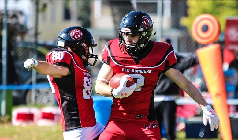 Andrew Heard, left, and Garrett Doucette celebrate Doucette's touchdown for the UNB Red Bombers in their 42-0 win over the UNBSJ Seawolves at College Field. UNB is 4-0 atop the Atlantic Football League.