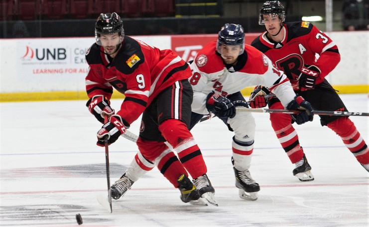UNB Reds rookie Austen Keating keeps the puck away from Acadia forward Eric Henderson in AUS men's hockey conference pre-season action. The teams meet at 7 p.m. Wednesday at the Aitken Centre.