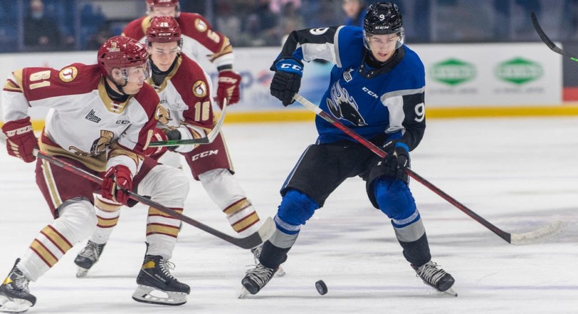 Acadie Bathurst Titan winger Bennett MacArthur, 61, lines up a hit on Saint John Sea Dogs forward Charles Savoie, 9, in their QMJHL game in the Port City on Oct. 9 as Titan centerman Dylan Andrews, 26, follows the play. The Titan won the game 4-3 in a shootout.