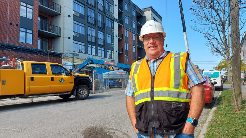 Developer Percy Wilbur stands in front of one of his uptown projects called The Wentworth building, a multi-residential development set to open Jan. 1, 2022. He says the cost of construction is a barrier to developing more affordable housing in Saint John.