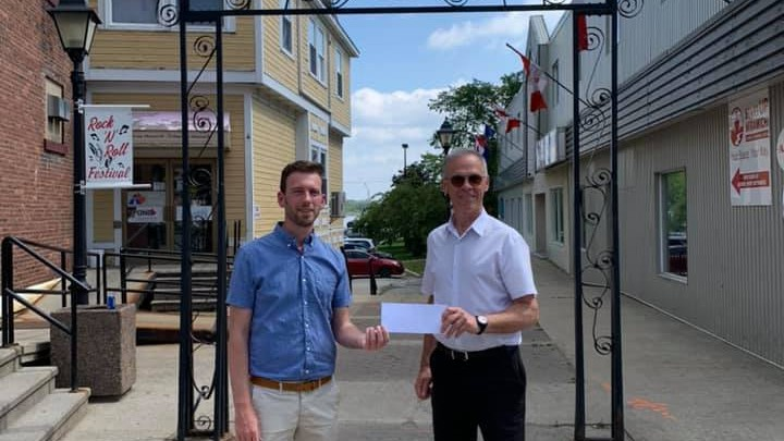 Miramichi Mayor Adam Lordon, left, accepts federal funding for the Fountain Head Lane project in downtown Newcastle from former Miramichi-Grand Lake MP Pat Finnigan in August. City council will vote Oct. 19 on funding agreements for Fountain Head Lane and a new bus for Miramichi Transit.