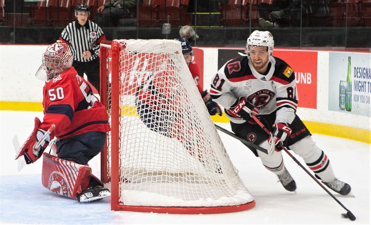 UNB Red centre James Phelan circles the net behind Acadia Axemen goalie Logan Flodell in AUS men's hockey conference action Wednesday night at the Aitken Centre. Phelan scored the tying goal as the Reds rallied for a 4-1 victory.