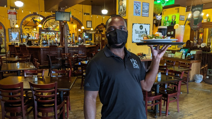 John Wa Kasaka brings a tray of drinks and food to a table at the Old Triangle Irish Alehouse on Thursday afternoon. Some bars and restaurants in the downtown core are struggling because many office workers have yet to return.