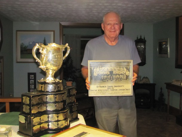 Tony McGuire poses with a team photo from his days with St. Francis Xavier University and the Memorial Cup after the Saint John Sea Dogs won in 2011.