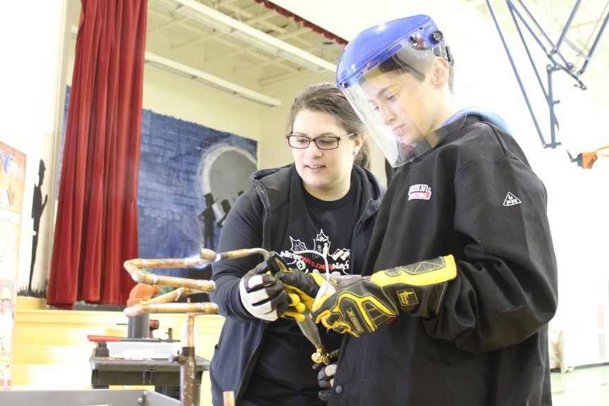 Morgan Smith, 11, had the chance to try his hand at soldering, with a little guidance from Tara Silliker of the Joint Apprenticeship Training Committee, during the skilled trade show, hosted by Skills Canada New Brunswick in this file photo.
