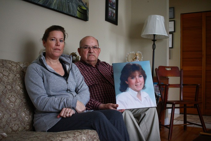 Laura Ann Davis was killed during a robbery in 1987. Her sister Brenda Davis and father Ron Davis are pictured in 2017 with a photo of her.