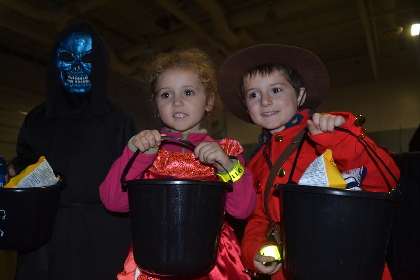 Olivier Johnson, left, Annabelle Johnson, and Frédérique Johnson, show off their bags of candy at the Monster Trot at the Moncton Coliseum in this file photo. This year's Monster Trot has been cancelled.