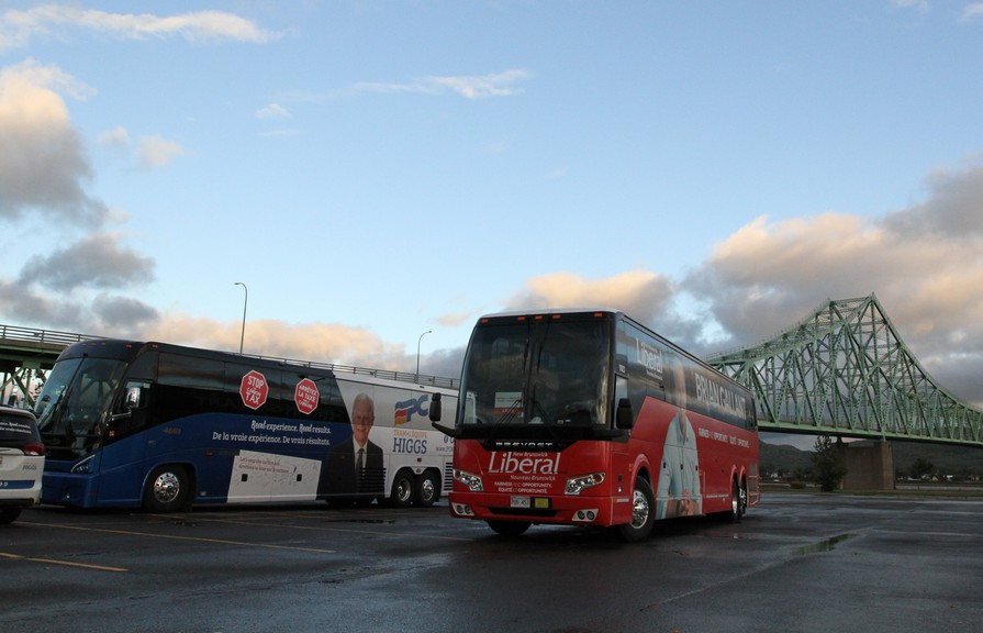 Both the Liberal and Progressive Conservative 2018 campaign buses are pictured in Campbellton with the J.C. Van Horne Bridge over the Restigouche River pictured in the background.