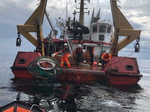 Staff from Fisheries and Oceans and the coast guard haul up a lost or abandoned snow crab trap during last summer's 'Operation Ghost.' Ottawa annouced $8.3 million in funding for a series of initatives to remove more abandoned gear from the ocean bed on Wednesday.