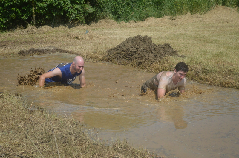 Alex Holjevac and Nick Burnett crawl through the mud on their way to the finish line during the 5 km obstacle course set up for the 2019 Tuff Muck Challenge in Perth-Andover. Registration is now open for this year's event, which is set for July 24.