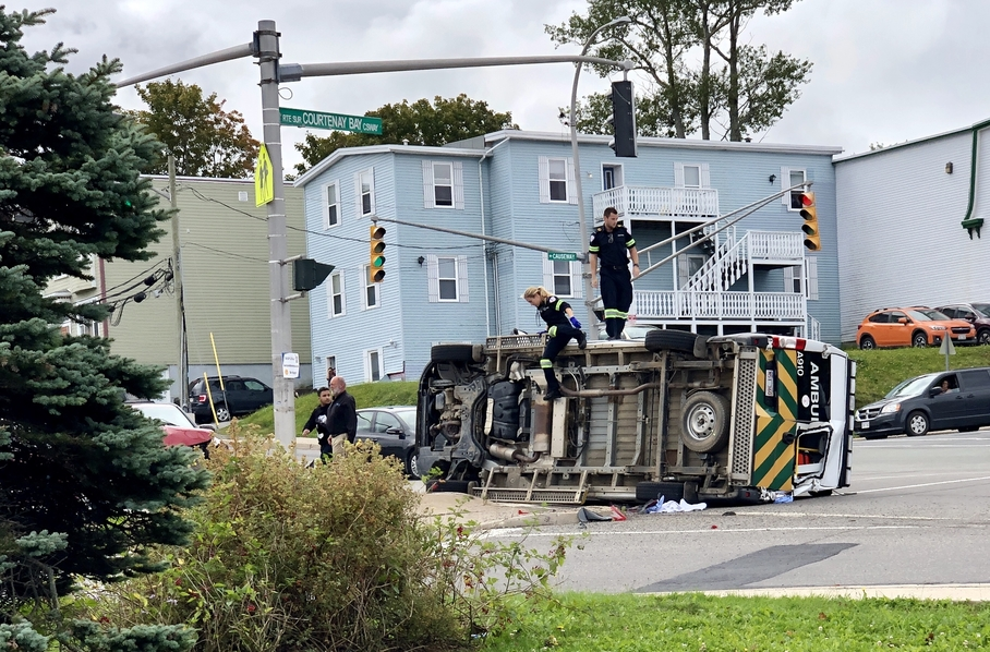 Paramedics Brittany Gionet and Mackenzie Holmes climb out of a flipped ambulance seconds after a two-vehicle collision that occurred at the intersection of Crown and Union Streets in Saint John on Sept. 17, 2019. Holmes was found not guilty of failing to stop at red light in connection to the collision on Wednesday.