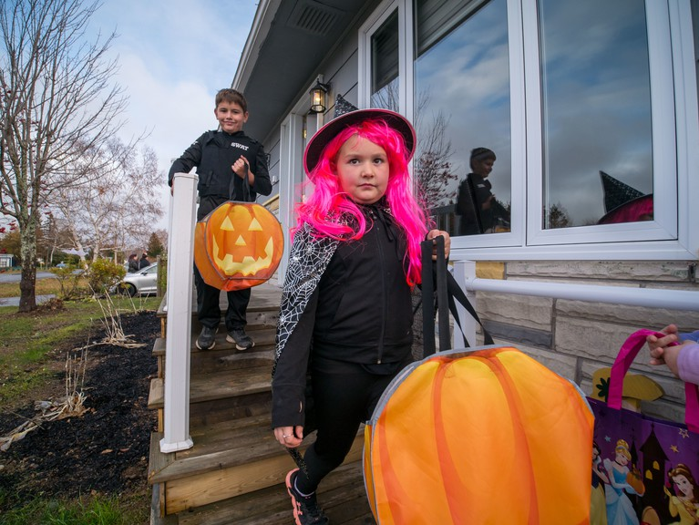 Bathurst's ghosts, monsters, witches and ghouls will be able to trick-or-treat this year, but given the pandemic that could be subject to change. Pictured is 10-year-old Alex Power and his sister Emilie,8, leaving a home after receiving their treats last year on Halloween. They are the children of Nadia Roussell.