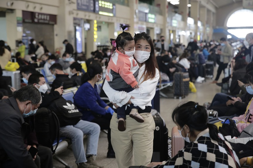 A woman wearing a protective mask carries a child as she walks past waiting travellers inside the Hankou railway station in Wuhan, China, on April 8, 2020. Ken McGeorge recounts how the Chinese government's reluctance to acknowledge the severity of the disease helped fuel its growth.
