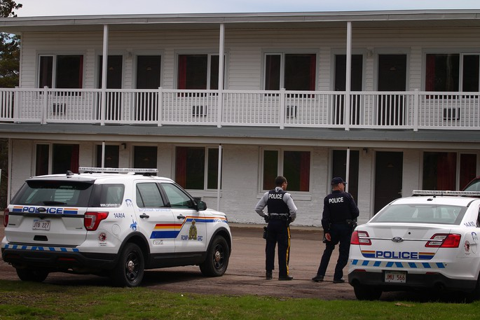 Codiac Regional RCMP members wait outside the Hotel Moncton, where several rooms were targeted by a drug investigation on May 15, 2020.