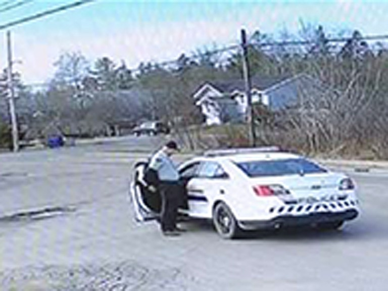 Gabriel Wortman, disguised as an RCMP officer next to his mocked-up RCMP cruiser, is seen on security footage.