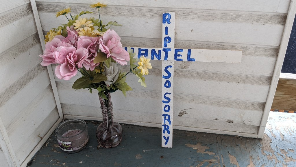 A small makeshift cross painted with the words RIP CHANTEL SO SORRY, a bouquet of plastic flowers and a candle are shown in the corner of Chantel Moore's balcony on June 11.