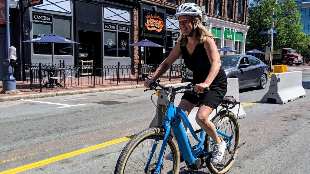Moncton Mayor Dawn Arnold rides her hybrid bicycle along Main Street Wednesday morning. Her bike uses pedal power to get started and an electric motor to maintain cruising speed.