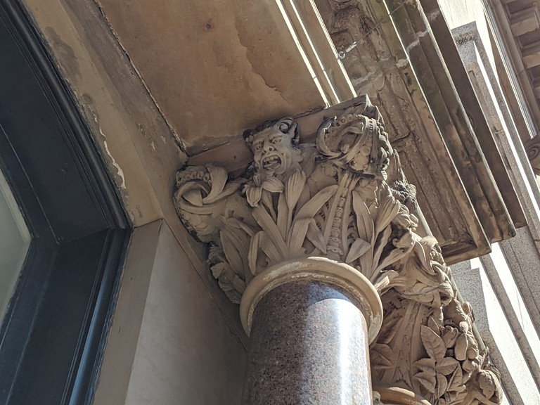 Just past the clearly marked 1915 Post Office, tucked under a pediment on the Palatine building, is the most curious carving in the city, the devil spitting out coins.