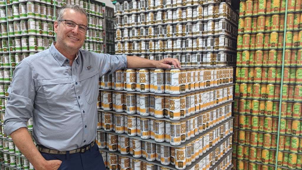 Marc Melanson, owner of Flying Boats Brewing, stands in front of hundreds of cans ready to be filled at his Dieppe brewery.