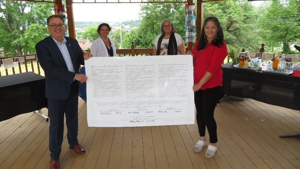 Jacques Paul Couturier, interim president and vice-chancellor of l'Université de Moncton (front left), and Patricia Bernard, Chief of the Madawaska Maliseet First Nation, are shown holding a Declaration of Commitment signed Monday.