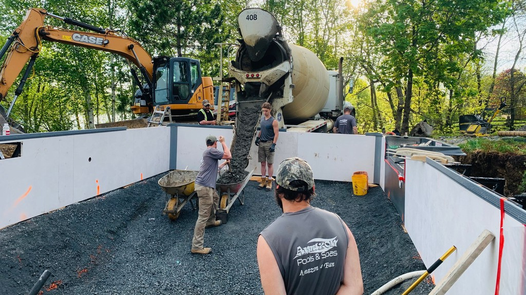 Increased demand for pools, coupled with manufacturing disruptions due to COVID-19, have led to long wait times for those wanting to have a pool installed. Pictured are staff with Amazon Pools and Spas installing an in-ground pool.