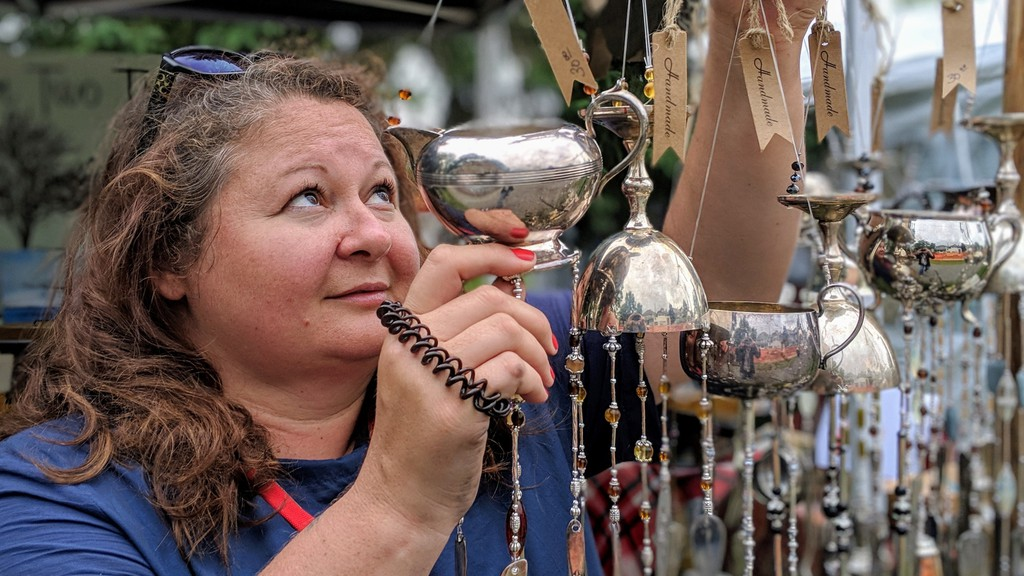 Karen Drover-Keddy of Hantsport, N.S. hangs wind chimes made of recycled silverware at the Victoria Park Arts & Crafts Fair in 2019. The event is cancelled this year.