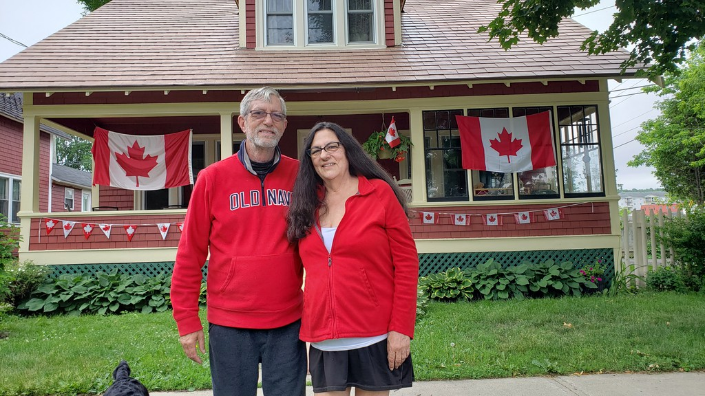 Peter and Sharlene Keith stand outside their home on Aberdeen Street in Fredericton, which is heavily decorated for Canada Day.