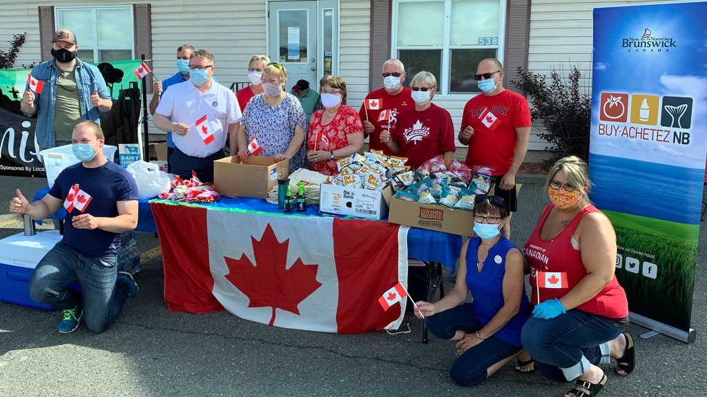Tobique-Mactaquac MP Richard Bragdon celebrates Canada Day with volunteers by handing out goodies to passersby outside his new Hartland office.