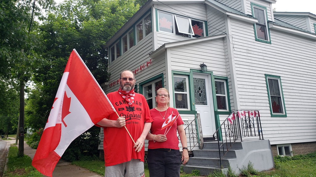 Jon Henry, left, and his wife, Jo Craig Henry, stand in front of their decorated house at McKeen Street on Fredericton's north side on Wednesday. Fredericton North has been declared in the winner over the south side of the city in the Canada Day house decorating challenge.