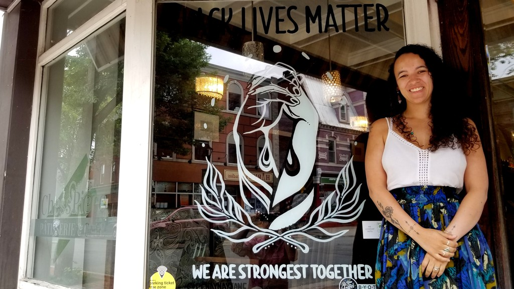 Frederictonartist Penny Heather stands beside the Black Lives Matter window display she painted for Chess Piece Patisserie& Cafe on Queen Street.